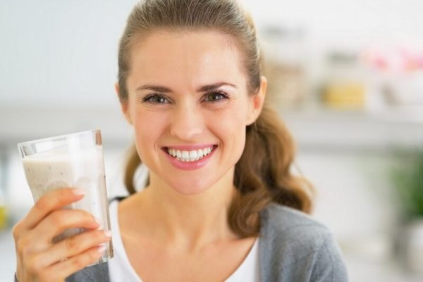 Woman holding a smoothie and smiling