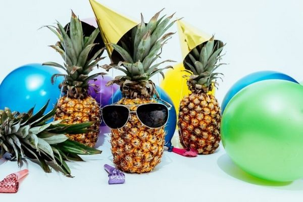Pineapples wearing sunglasses surrounded by balloons